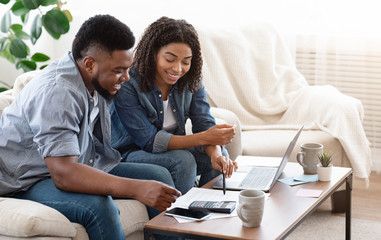 Smiling Black Couple Discussing Total Amount Of Their Spends At Home