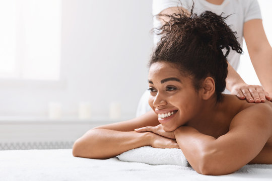 Smiling woman having back massage and looking at copy space