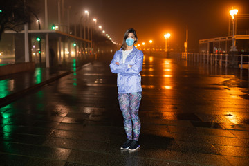 Condifent female athlete on urban night fitness and running workout wearing face mask against Covid-19.