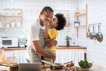 African Cute little boy in yellow casual kissing Dad while cooking at home together. Happy smiling African-American Father while hug and carry his son in kitchen. Joyful Black family, Love emotion.