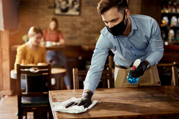 Fototapeten Restaurant Waiter with protective face mask disinfecting tables in a pub.