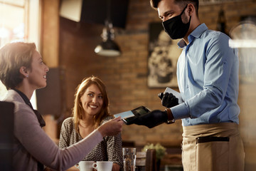 Female customer making contactless payment to a waiter in a cafe.