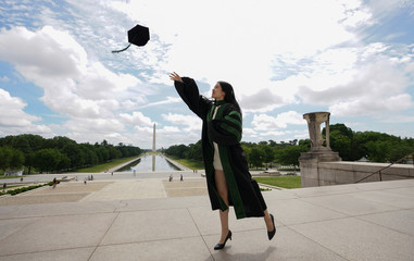 Georgetown University medical school graduate He Zhou casts her cap into the air  at the Lincoln Memorial in Washington