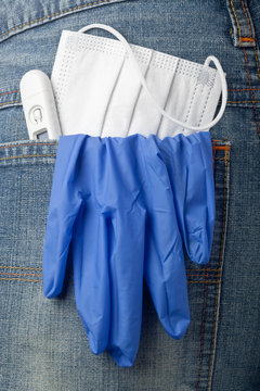 Facial mask, thermometer and latex glove in back pocket