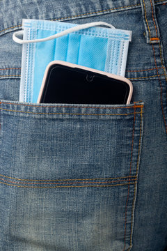 Facial mask and mobile phone in jeans back pocket;