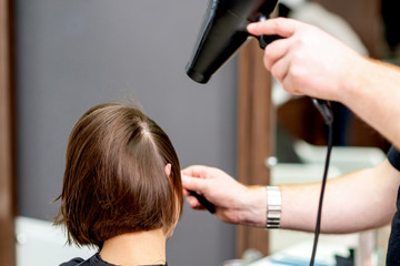 Hairdresser's hands drying short brown hair with blow dryer in hair salon.