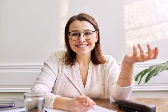 Woman teacher, mentor, psychologist looking at webcam of digital tablet