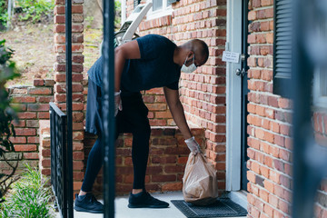 Gig economy food contactless delivery man dropping off food at front doorstep