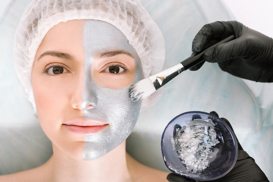 Nice woman looks directly into the camera while lying on a cosmetology table and applying a silver beauty mask to her skin with a brush. Skin cleansing and rejuvenation concept