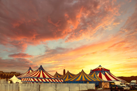 Red and white circus tents topped with bleu starred cover against a sunny blue sky with clouds