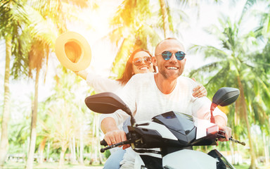 Laughing happy couple travelers riding motorbike during their tropical vacation in Thailand under palm trees. Woman raised hands up with hat.