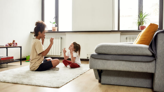 Healthcare. African american woman baby sitter and caucasian cute little girl doing yoga at home