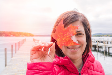 Portrain of a smiling woman holding a red maple leaf in front of one of her eyes. A deserted wooden jetty on a lake is visible in background. Lakes region, NH, USA.