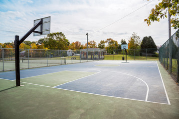 Empty basketball court in a public park in a residential district on a sunny autumn morning