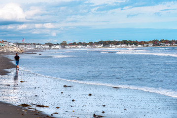 Beautiful sandy beach crowded with surfers on a partly cloudy autumn day. Portsmouth, NH, USA.