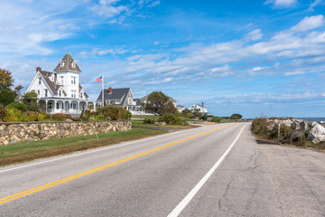 Empty coast road lined with beautiful houses on a clear autumn day. New England, USA.