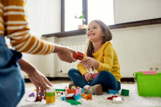Fun and play all day. Caucasian little girl spending time with african american baby sitter, playing with construction toys set, sitting on the floor