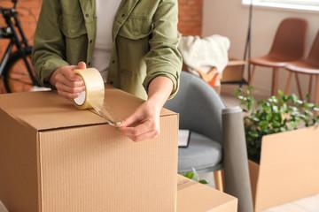 Fototapeta Woman packing moving box at home