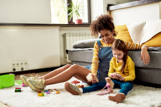 Play all day. African american woman baby sitter entertaining caucasian cute little girl. They are playing with dolls, sitting on the floor