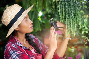 A portrait of a beautiful asian woman wears hat in the nursery while she takes care of the cactus before selling. Wall mural
