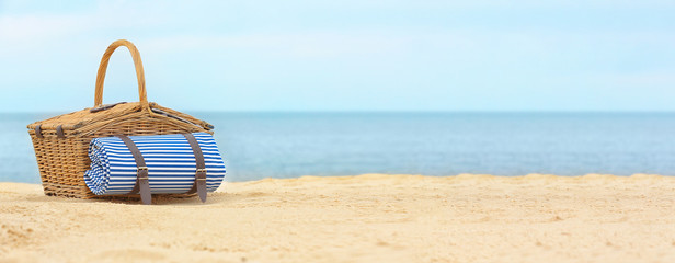 Wicker picnic basket with blanket on sand near sea, space for text. Banner design