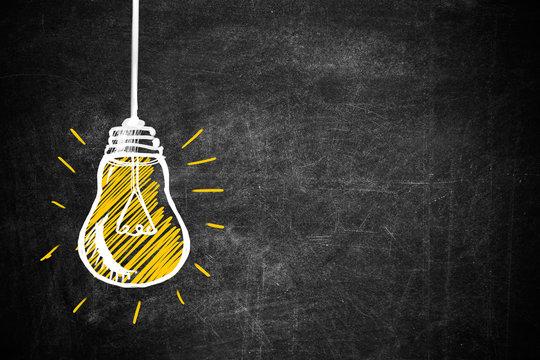 Light bulb drawing as symbol of idea on chalkboard
