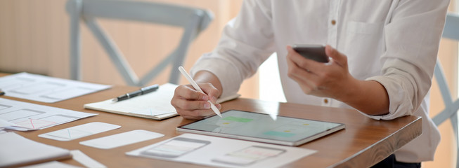 Wall Mural - Cropped shot of professional UI developer working on mock-up tablet, smartphone and paperwork