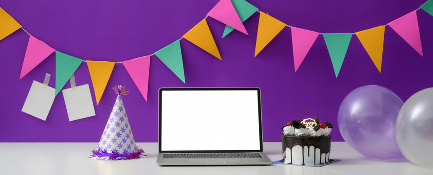 Online birthday party concept with blank screen laptop, cake, party hat and balloon
