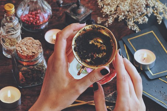Wiccan witch holding a golden teacup for tea leaf scrying, divination, future reading. Black tea residue in the bottom of a cup, passable for coffee grounds. Witchy vibe with dried herbs and flowers