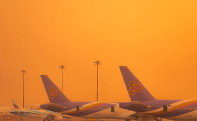 BANGKOK, THAILAND-FEBUARY 20, 2019 : Thai Airways Airlines. Commercial airplane parked at the airport with orange sunset sky. Global aviation business crisis from coronavirus. Air transportation.