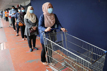 Shoppers wearing protective face masks wait in a line to enter a supermarket, amid the coronavirus disease (COVID-19) outbreak in Kuala Lumpur
