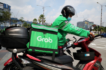 A GrabFood rider gets ready for a delivery outside a shopping mall, amid the coronavirus disease (COVID-19) outbreak in Kuala Lumpur