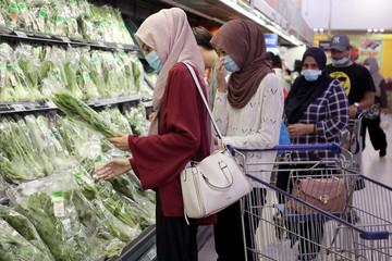 Shoppers wearing protective face masks shop at a supermarket, amid the coronavirus disease (COVID-19) outbreak in Kuala Lumpur