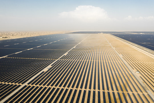 Aerial view of a landscape with photovoltaic solar panel farm producing sustainable renewable energy in a desert power plant in daylight.