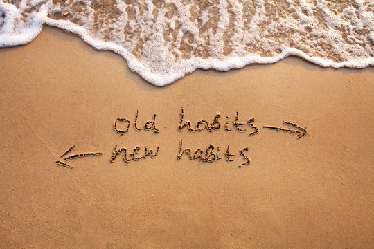old habits vs new habits, life change concept written on sand