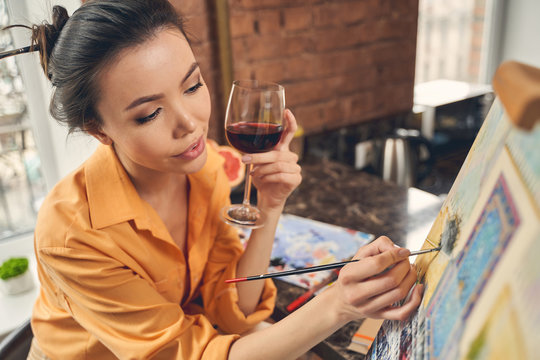 Beautiful lady drinking wine and painting on canvas