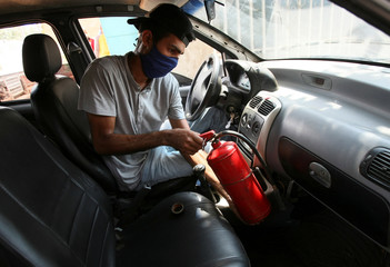 Moises Vilchez holds a fire extinguisher inside his car, that runs with cooking gas instead of fuel, as Venezuelans are struggling to cope with chronic fuel shortage, in Maracaibo