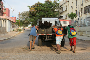 Men push a truck that run out of fuel as Venezuelans are struggling to cope with chronic fuel shortage, in Maracaibo