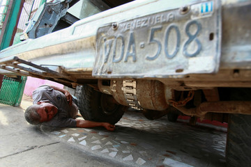 Alfredo Gonzalez checks a cooking gas canister beneath his car, which is used to run his vehicle instead of fuel, as Venezuelans struggling to cope with chronic fuel shortage, in Maracaibo