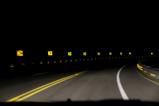 A series of yellow reflective 'sharp turn' signs being lit up by the lights of an oncoming car. The pitch black night sky is in contrast with the signs and street. Concept of speed and car accidents.
