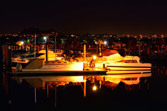 Boats moored in Auckland marina at night. Selective focus