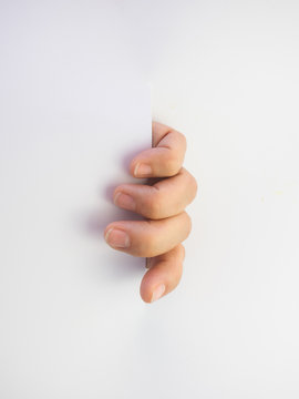 Close up of hand coming out of slot in white paper