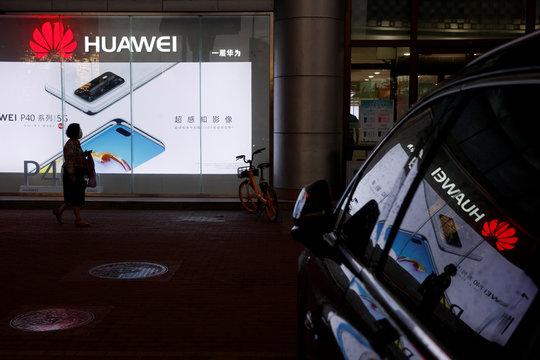 A woman walks past a Huawei store in Beijing