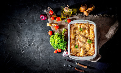 Traditional italian lasagna with vegetables, minced meat and cheese On a dark background. Homemade meat lasagna. Top view wiht copy space