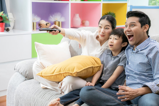 Happy Asian family watching television together at living room