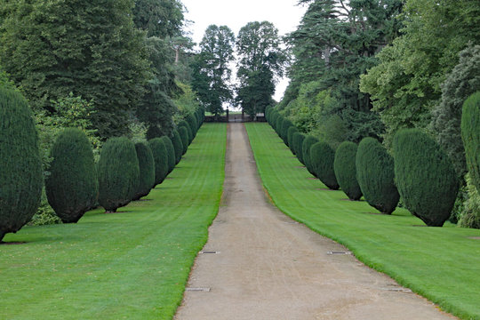 Long straight driveway to the gates at the entrance to an English manor house.