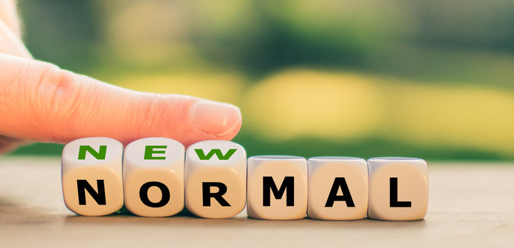 """New normal concept. Hand turns dice and changes the expression """"normal"""" to """"new normal""""."""