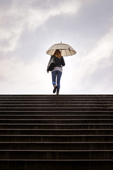 Stairway to heaven. Woman with umbrella walking at staircase in rain