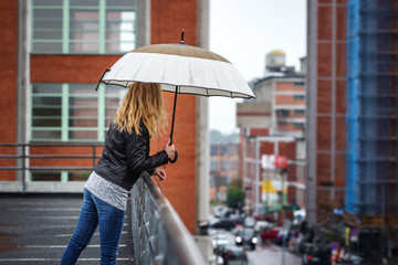 Woman with umbrella looking at city street in rain