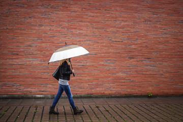 Trendy woman with umbrella is walking next to red brick wall in rain